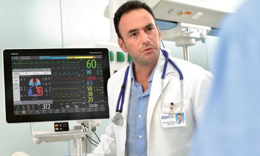 Médico monitoreando paciente en UCI.